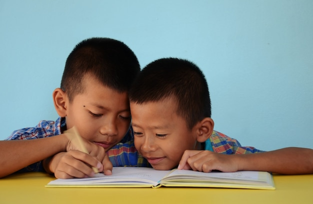 Dwóch chłopców odrabia lekcje razem z przyjacielskim radosnym i zabawnym