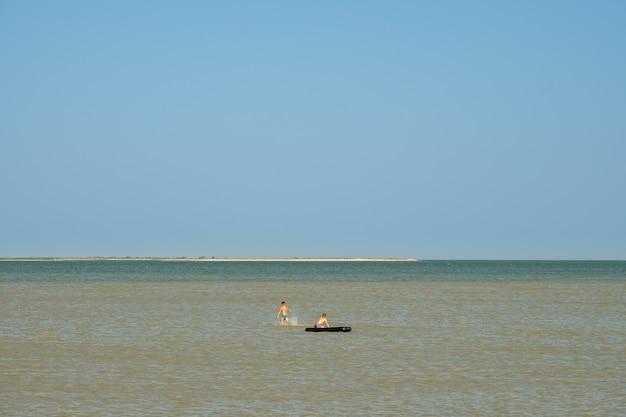 Dwóch chłopców pływa razem w morzu na materacu wodnym. dzieci pływają w płytkiej wodzie na słonecznym wybrzeżu. szczęśliwe dzieciństwo.