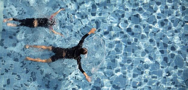Dwóch chłopców pływających w basenie razem
