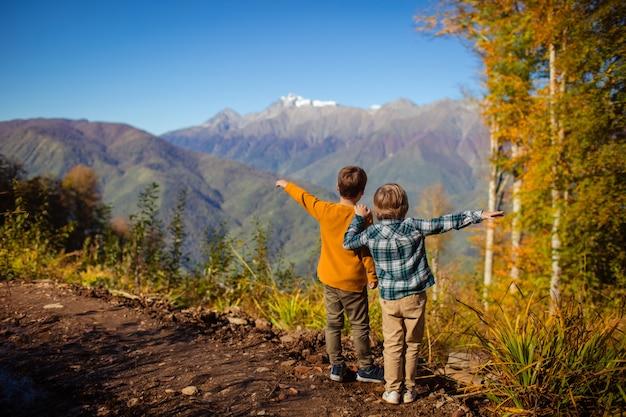 Dwóch chłopców podnoszących ręce i patrzących na góry