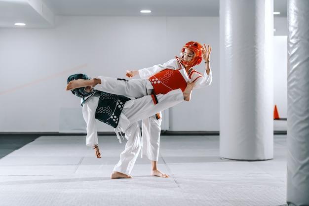 Dwóch chłopców rasy białej w taekwondo kopie i walczy na treningach.