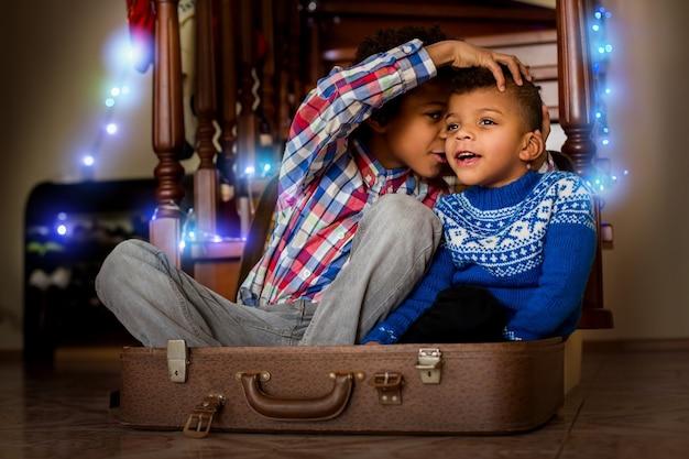Dwóch chłopców siedzących i szepczących. afro dzieci szepczą i uśmiechają się. teraz znasz sekret. pozwól, że coś ci wyjaśnię.