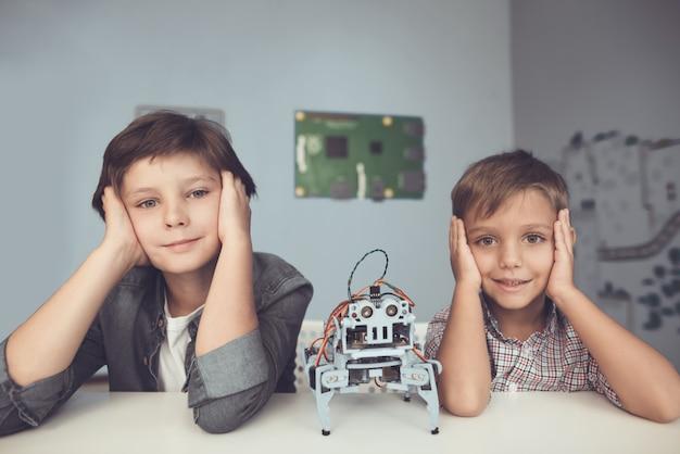 Dwóch chłopców siedzących przy stole i konstruujących robota.
