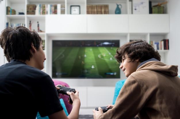 Dwóch chłopców siedzących w domu i grających w gry wideo na konsoli do gier