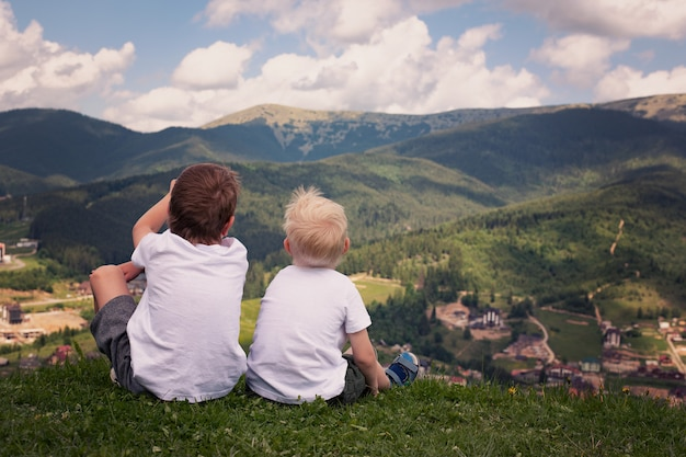 Dwóch chłopców siedzi na wzgórzu i patrzy na góry.