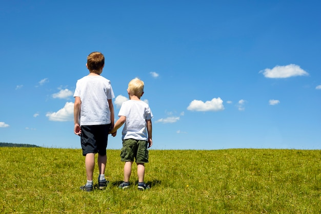 Dwóch chłopców stojących na łące, trzymając się za ręce