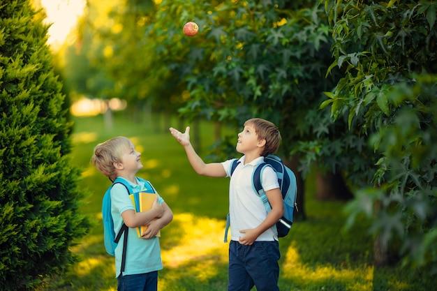 Dwóch chłopców szczęśliwy uczeń zabawy na spacerze w parku i rzucanie jabłkiem