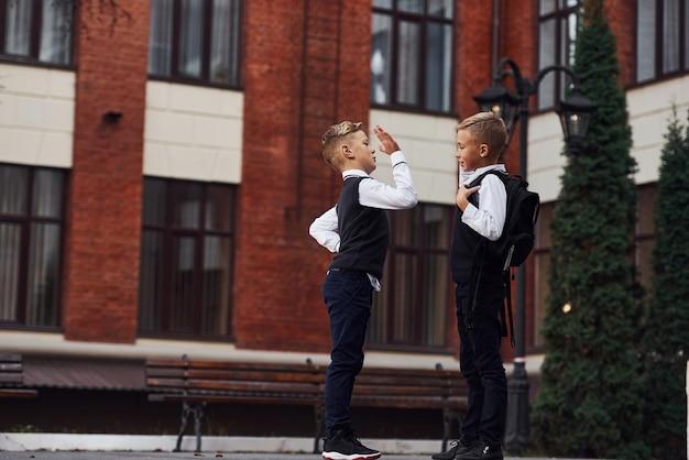 Dwóch chłopców w mundurkach szkolnych, które są na zewnątrz, razem przybijają piątkę w pobliżu budynku edukacyjnego.