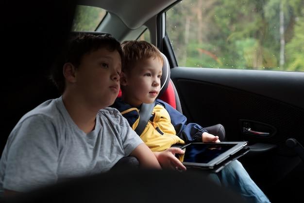 Dwóch chłopców w samochodzie z tabletem pc