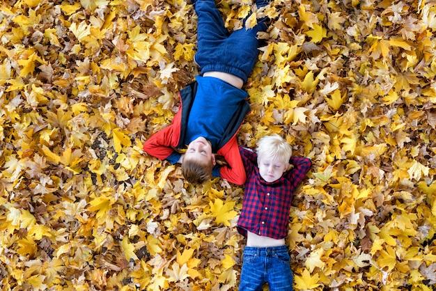Dwóch chłopców z zamkniętymi oczami leży w żółtych jesiennych liściach