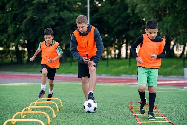 Dwóch chłopców ze szkoły biegnie po murawie podczas letniego obozu piłkarskiego. intensywny trening piłkarski z trenerem.