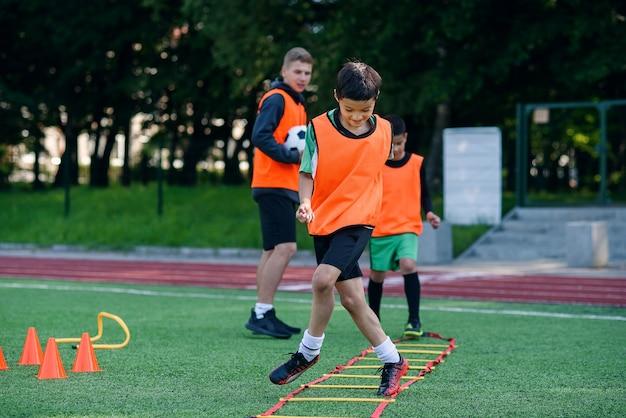 Dwóch chłopców ze szkoły prowadzi ćwiczenia drabinkowe podczas letniego obozu piłkarskiego.