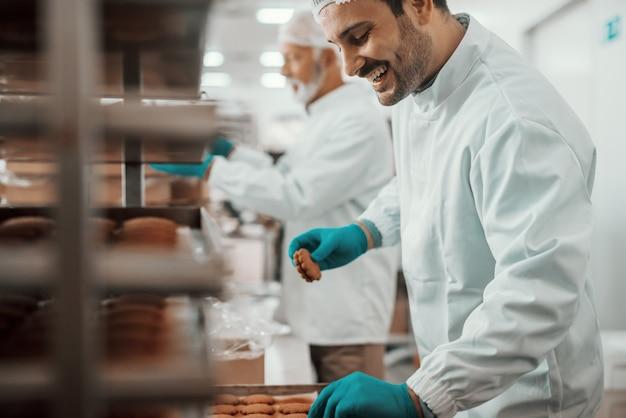 Dwóch ciężko pracujących oddanych pracowników rasy kaukaskiej ubranych w białe sterylne mundury zbierające i pakujące ciasteczka w pudełka. wnętrze zakładu spożywczego.