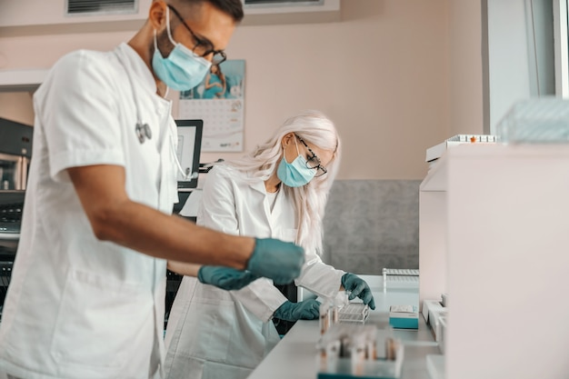 Dwóch ciężko pracujących pracowników medycznych trzymających probówki z próbkami krwi i pracujących nad lekiem na groźną chorobę.