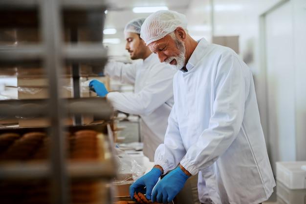 Dwóch ciężko pracujących pracowników zakładu spożywczego w sterylnych mundurach pakujących ciasteczka w pudełka.