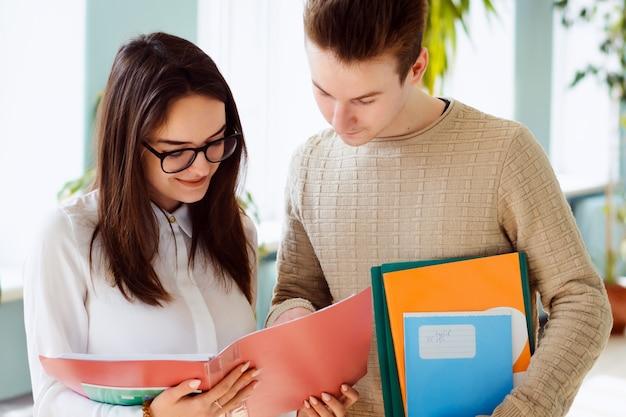 Dwóch ciężko pracujących studentów omawiających pewne sprawy stojących na korytarzu, trzymających w rękach foldery i materiały dydaktyczne