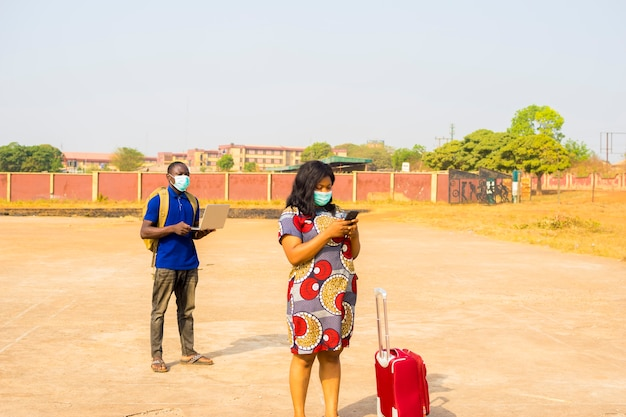 Dwóch czarnych afrykańskich podróżników w maskach na twarzach praktykujących dystans społeczny za pomocą telefonu komórkowego.