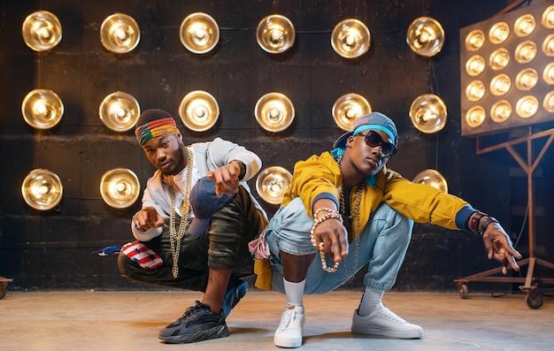 Dwóch czarnych raperów siedzących na podłodze