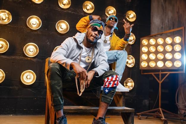 Dwóch czarnych raperów siedzących na schodach