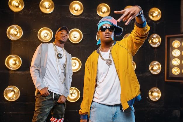 Dwóch czarnych raperów w czapkach na scenie z reflektorami