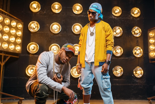 Dwóch czarnych raperów w czapkach, występ w klubie, scena z reflektorami