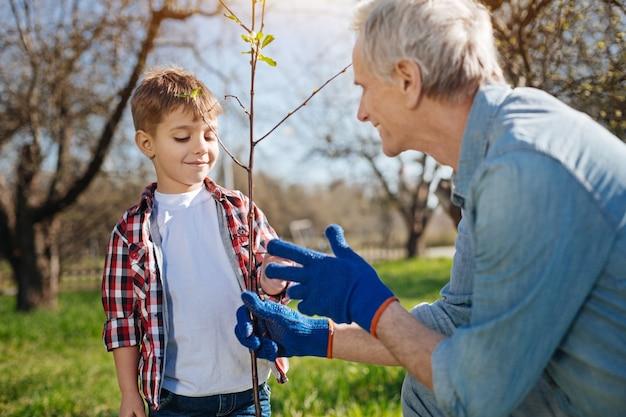 Dwóch członków rodziny męskiej dba o przyrodę, wspólnie pracując w ogrodzie na wiejskim podwórku