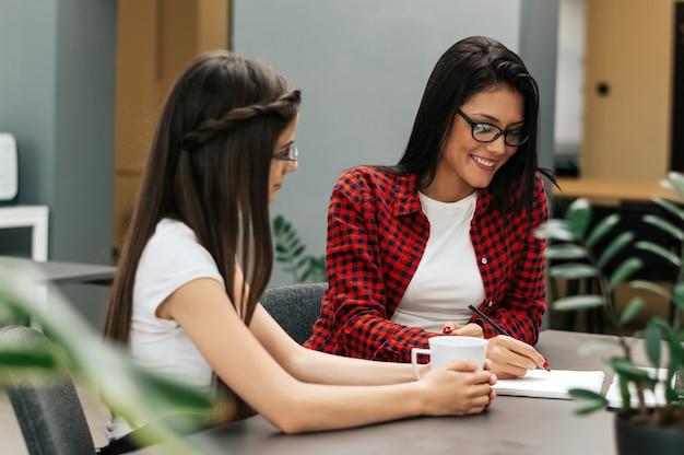 Dwóch dedykowanych młodych przedsiębiorców kobiet pracujących razem w biurze.