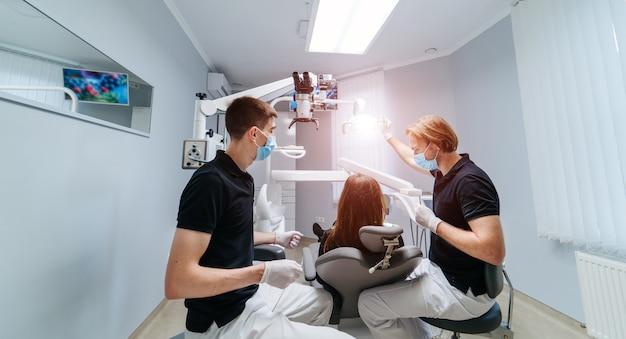Dwóch dentystów bada zęby pacjenta w celu dalszego leczenia.