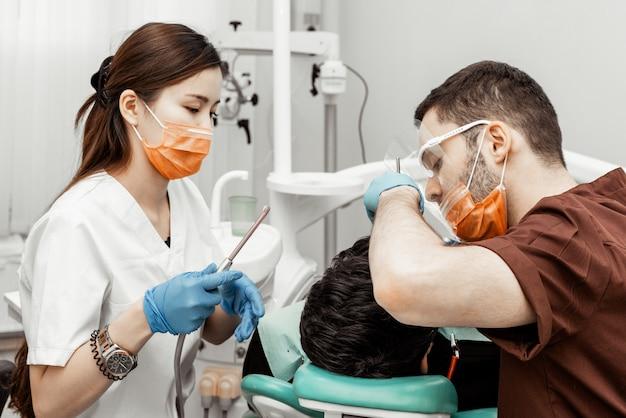 Dwóch dentystów leczy pacjenta. profesjonalny uniform i wyposażenie dentysty. służba zdrowia wyposażenie miejsca pracy lekarzy. stomatologia