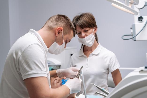 Dwóch dentystów przeprowadza leczenie stomatologiczne zębów młodych pacjentek w fotelu.