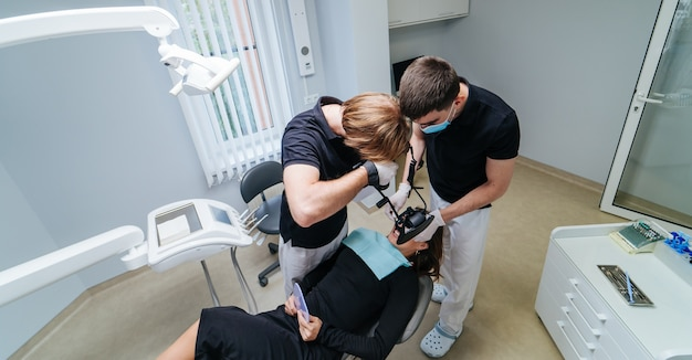 Dwóch dentystów z narzędziami dentystycznymi leczy zęby pacjenta w gabinecie stomatologicznym. koncepcja medycyny, stomatologii i opieki zdrowotnej. higiena jamy ustnej. widok z boku.
