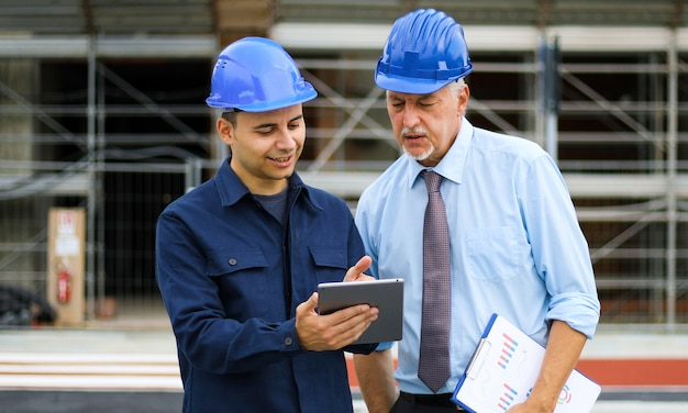Dwóch deweloperów architektów przeglądających plany budynków na budowie za pomocą tabletu
