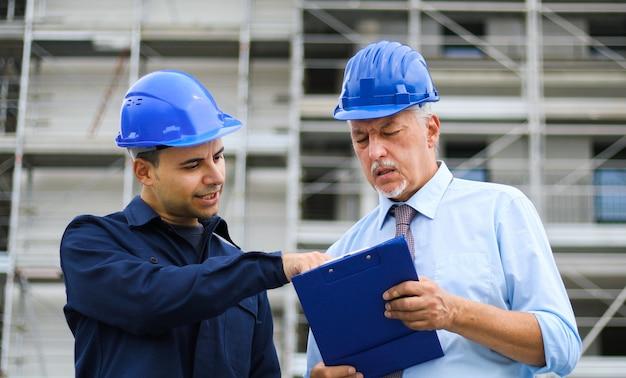 Dwóch deweloperów architektów przeglądających plany budynków na budowie