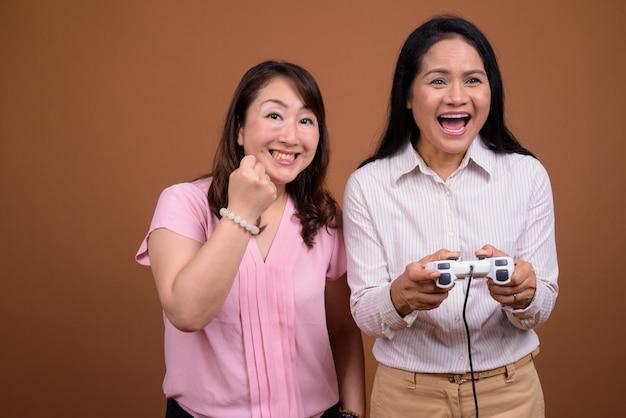 Dwóch dojrzałych azjatyckich przedsiębiorców razem przed brązową ścianą
