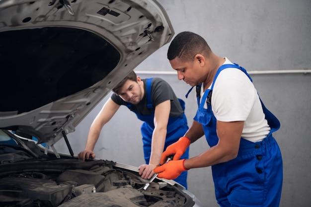 Dwóch doświadczonych mechaników naprawia uszkodzony silnik samochodu
