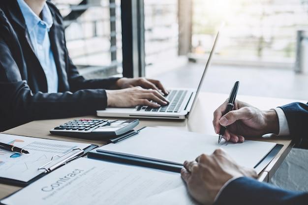 Dwóch dyrektorów wykonawczych omawiających statystyki finansowe sukcesu firmy