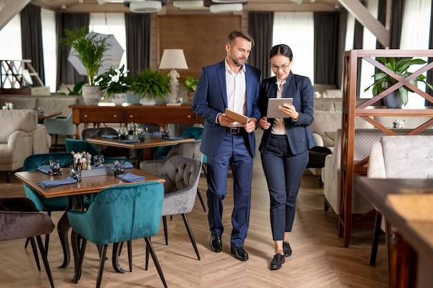 Dwóch eleganckich partnerów biznesowych spacerujących po luksusowej restauracji i przewijających dane na panelu dotykowym podczas omawiania danych online