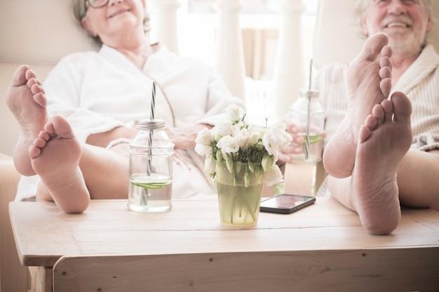 Dwóch emerytów lub seniorów siedzi wewnątrz ośrodka lub hotelu podczas zabiegu kosmetycznego - zbliżenie stóp na stole z koktajlem