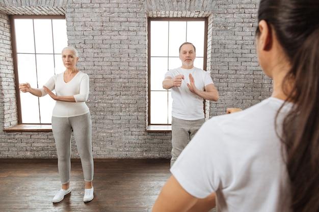 Dwóch emerytów robi ćwiczenia jogi z wyprostowanymi plecami, stojąc za swoim nauczycielem