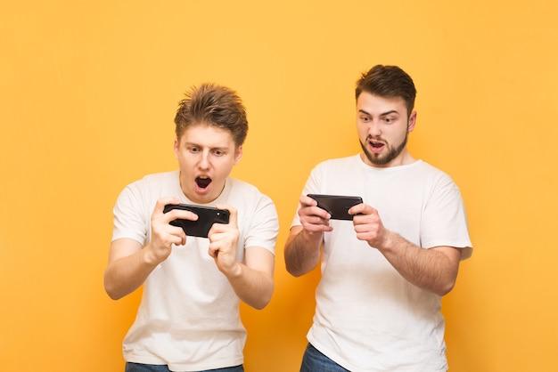 Dwóch emocjonalnych chłopców jest na żółto i grają w gry mobilne na smartfonach