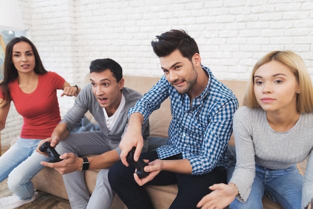 Dwóch facetów i dwie dziewczyny grają na konsoli do gier.