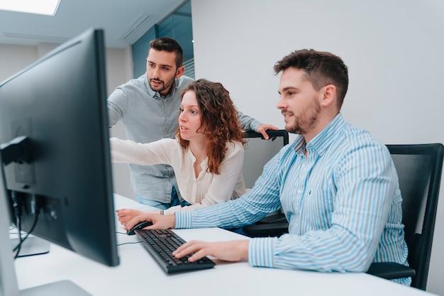 Dwóch facetów i współpracownicy kobiety patrzą na komputer, próbując rozwiązać problem