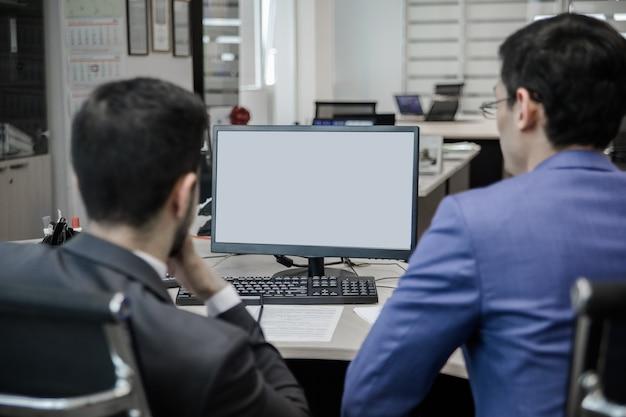 Dwóch facetów przy komputerze w call center za ladą.