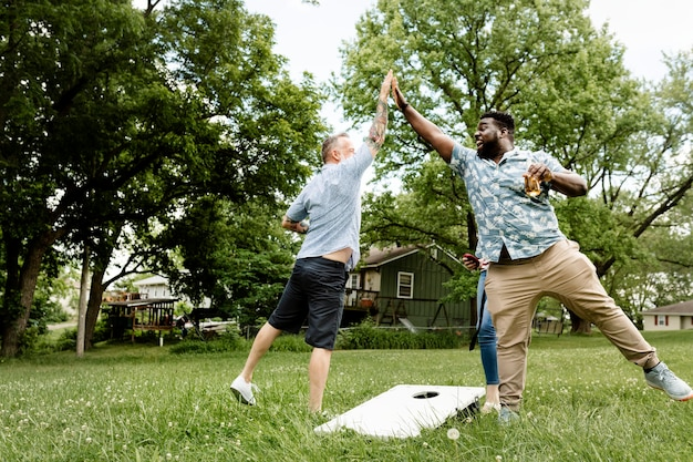 Dwóch facetów przybija sobie piątkę na letniej imprezie