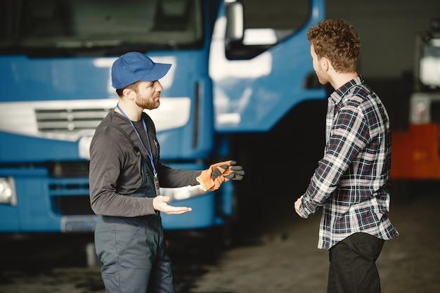Dwóch facetów rozmawia o pracy. pracować w garażu w pobliżu ciężarówki. przekazywanie dokumentów wraz z towarem