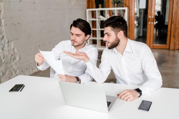 Dwóch facetów w biurze omawiających dokumenty biznesowe i porozumienie