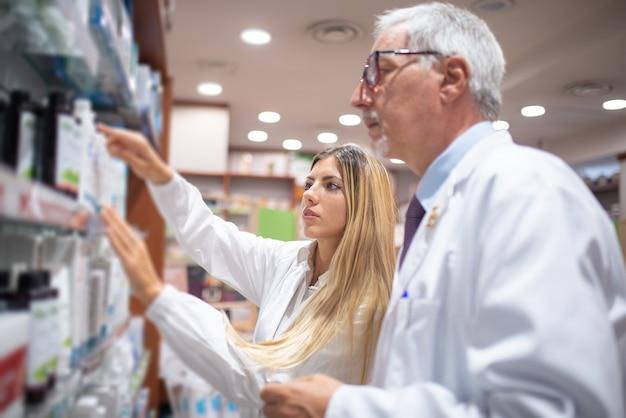 Dwóch farmaceutów sprawdza stan magazynowy w swojej aptece