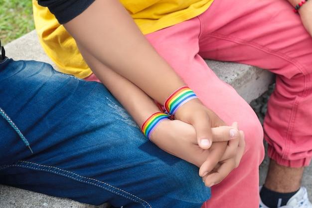 Dwóch gejów siedzących trzymających się za ręce z flagą dumy w dłoniach