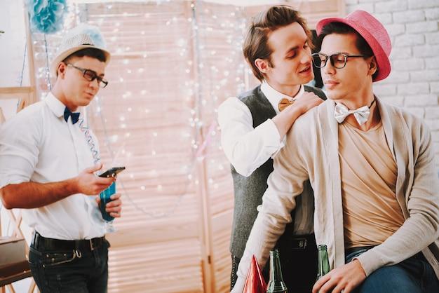 Dwóch gejów w muszkach figlarnie flirtuje na imprezie.