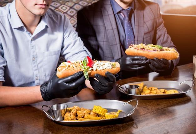Dwóch głodnych młodych mężczyzn jedzących hot dogi w kawiarni. restauracja